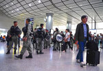 Riot police stand guard at the airport express central station in downtown Hong Kong, Saturday, Sept. 7, 2019. Hong Kong authorities were limiting airport transport services and controlling access to terminals Saturday as they braced for a second weekend of disruption following overnight demonstrations that turned violent. (AP Photo/Vincent Yu)