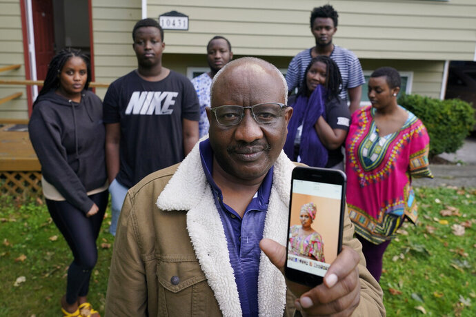 Sophonie Bizimana, center, a permanent U.S. resident who is a refugee from Congo, poses for a photo, Wednesday, Oct. 14, 2020, at his home in Kirkland, Wash., along with six of his children as he displays a cell-phone photo of his wife, Ziporah Nyirahimbya, who is in Uganda and has been unable so far to join him in the U.S. For decades, America admitted more refugees annually than all other countries combined, but that reputation has eroded during Donald Trump's presidency as he cut the number of refugees allowed in by more than 80 percent. (AP Photo/Ted S. Warren)