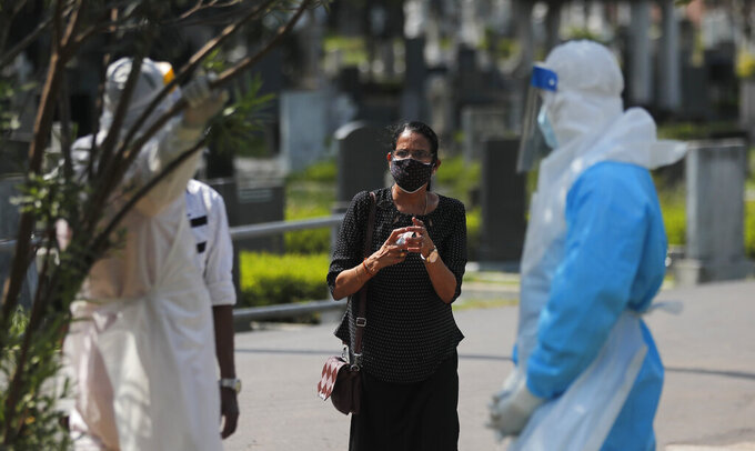 A Sri Lankan woman speaks to health workers as she attempts to attend the cremation of her family member who died of COVID-19 in Colombo, Sri Lanka, Wednesday, Feb. 10, 2021. (AP Photo/Eranga Jayawardena)
