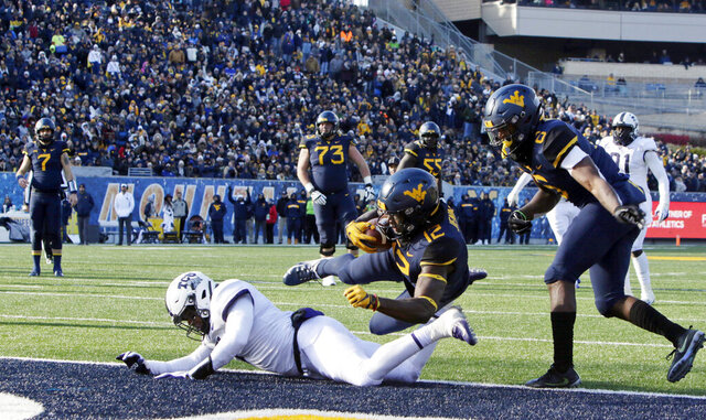 FILE - In this Nov. 10, 2018, file photo, West Virginia wide receiver Gary Jennings Jr. (12) jumps over TCU linebacker Arico Evans (7) to score a touchdown during the second half of an NCAA college football game in Morgantown, W.Va. TCU and West Virginia, who meet this week, came into the Big 12 together in 2012, and have split their eight games as conference foes. TCU, coming off its first home win, is 3-0 on the road with all of those being conference games. But the Frogs lost by 37 and 24 points in their last two trips to Morgantown. (AP Photo/Raymond Thompson, File)