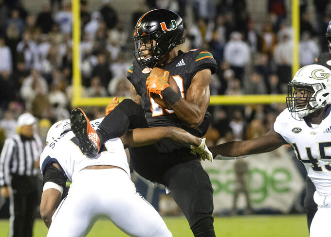 Miami wide receiver Lawrence Cager makes a catch as he comes down on Georgia Tech defensive back Lamont Simmons, with defensive back Charlie Thomas (45) moving in during the first quarter of an NCAA college football game Saturday, Nov. 10, 2018, in Atlanta. (AP Photo/John Amis)