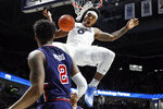 Xavier's Tyrique Jones (0) dunks as St. John's Shamorie Ponds (2) watches in the first half of an NCAA college basketball game, Saturday, March 9, 2019, in Cincinnati. (AP Photo/John Minchillo)
