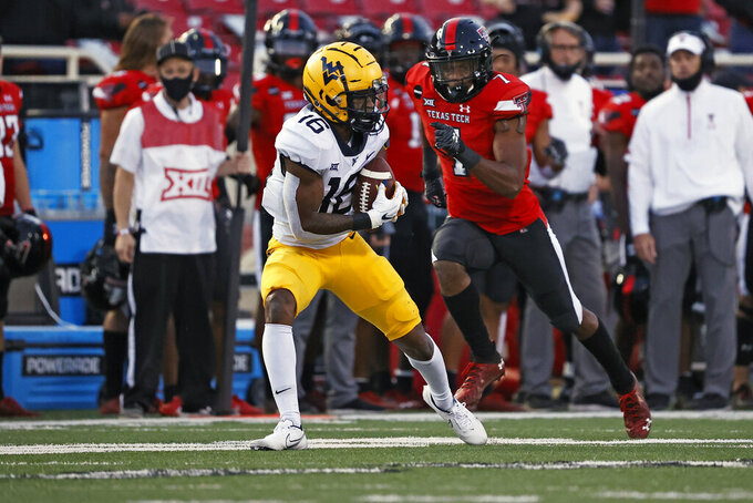 West Virginia's Winston Wright Jr. (16) catches a pass during the second half of an NCAA college football game against Texas Tech, Saturday, Oct. 24, 2020, in Lubbock, Texas. (AP Photo/Brad Tollefson)