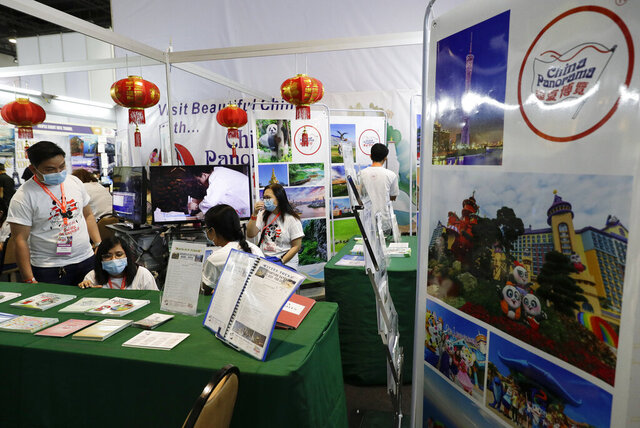 Workers wearing protective masks sit inside their booth promoting China during a travel fair in Manila, Philippines on Friday, Feb. 7, 2020. The organizer said the impact of travel bans due to the new virus has already affected tourism in the Philippines due to the huge Chinese market. Asian nations have profited handsomely from the impressive growth in tourists from China over the past decade, but the specter of a rapidly spreading virus has raised concerns over the industry prospects. (AP Photo/Aaron Favila)