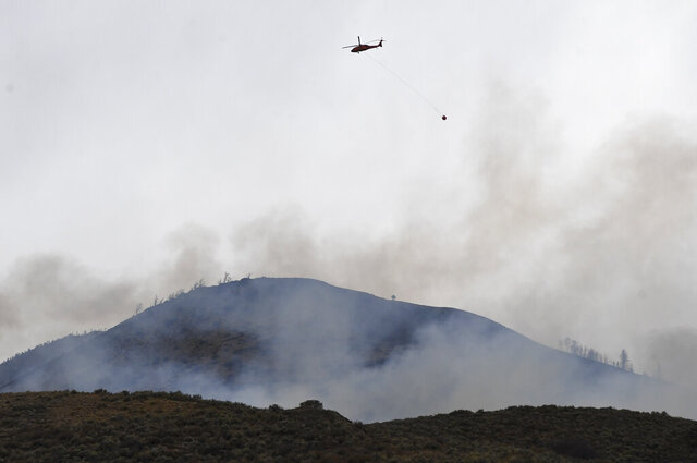 A helicopter makes a water drop on the East Troublesome Fire, Saturday, Oct. 24, 2020 in Granby, Colo.  The East Troublesome Fire has consumed over 200,000 acres with 4 percent containment ahead of an impending winter storm. (Andy Cross/The Denver Post via AP)