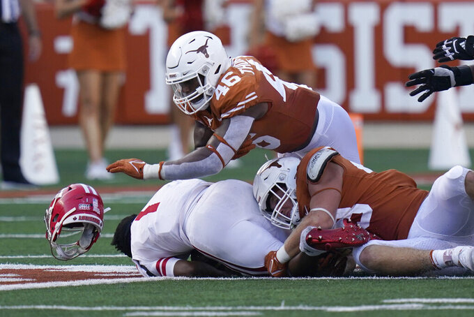 Louisiana-Lafayette quarterback Levi Lewis (1) loses his helmet as he is sacked by Texas linebacker Ray Thornton (46) and safety Zach Edwards (43) during the second half of an NCAA college football game Saturday, Sept. 4, 2021, in Austin, Texas. (AP Photo/Eric Gay)