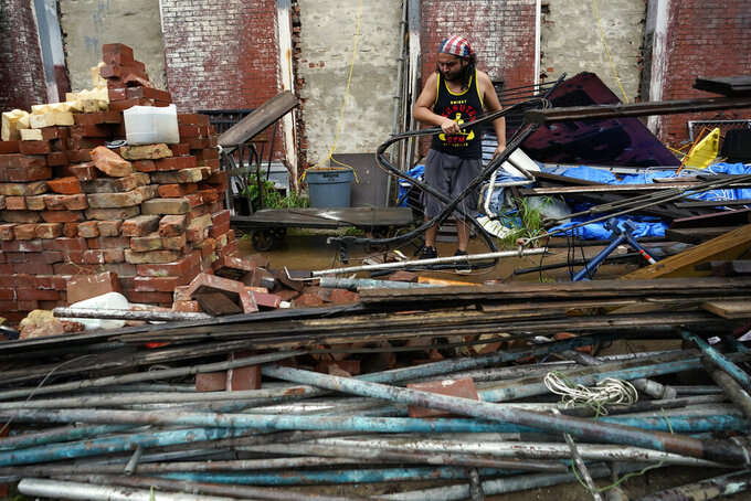 Adrian Bentancourt cleans up debris from a fence that was blow down by Hurricane Nicholas Tuesday, Sept. 14, 2021, in Galveston, Texas. (AP Photo/David J. Phillip)