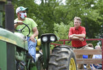 Brice Gieringer, left, drives a tractor as Rep. Roger Marshall, front right, who represents the Kansas First Congressional District, tours Gieringers Family Orchard & Berry Farm on Thursday, July 9, 2020, in Edgerton, Kan., in Johnson County. Marshall, a Republican, is running for the seat in the U.S. Senate being vacated Sen. Pat Roberts. Members of the Kansas Farm Bureau were also on the tour. (Tammy Ljungblad/The Kansas City Star via AP)