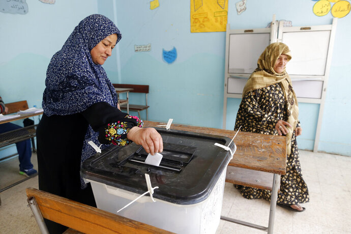 A voter casts her ballot on constitutional amendments during the second day of three-day voting at polling station in Cairo, Egypt, Sunday, April 21, 2019. Egyptians are voting on constitutional amendments that would allow President Abdel-Fattah el-Sissi to stay in power until 2030.(AP Photo/Amr Nabil)