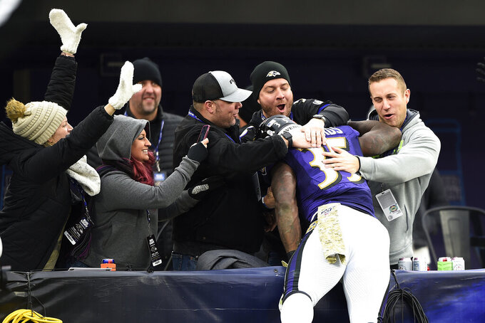 Baltimore Ravens running back Gus Edwards jumps onto fans after running for a touchdown against the Houston Texans during the second half of an NFL football game, Sunday, Nov. 17, 2019, in Baltimore. (AP Photo/Gail Burton)