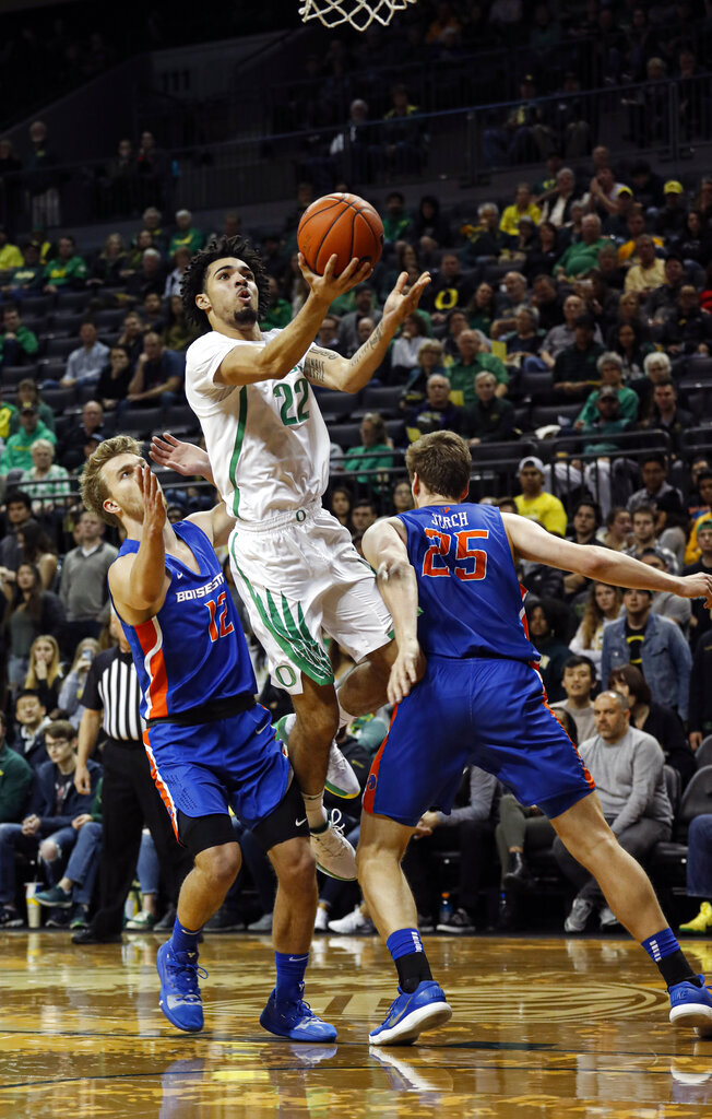 Oregon guard Addison Patterson (22) drives against Boise State guard Max Rice (12), and center Robin Jorch (25), in an NCAA college basketball game Saturday, Nov. 9, 2019, in Eugene, Ore. (AP Photo/Thomas Boyd)