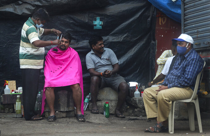 A roadside barber wearing mask as a precaution against the coronavirus gives hair cut to a man as others wait for their turn in Mumbai, India, Sunday, Jan. 3, 2021. India authorized two COVID-19 vaccines on Sunday, paving the way for a huge inoculation program to stem the coronavirus pandemic in the world's second most populous country. (AP Photo/Rafiq Maqbool)