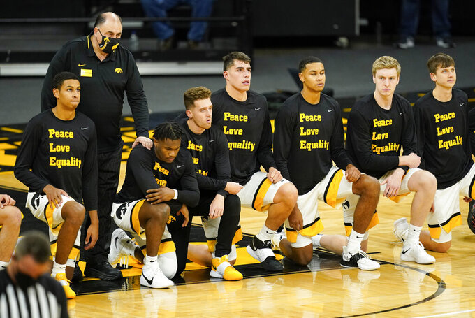 Iowa players kneel on the court before the playing of the national anthem before an NCAA college basketball game against North Carolina Central, Wednesday, Nov. 25, 2020, in Iowa City, Iowa. (AP Photo/Charlie Neibergall)