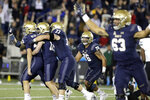 Navy kicker Bijan Nichols, far left, is congratulated by teammates as they celebrate his game-winning field goal as time expires during an NCAA college football game against Tulane, Saturday, Oct. 26, 2019, in Annapolis. Navy won 41-38. (AP Photo/Julio Cortez)
