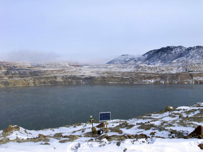 FILE - In this Dec. 14, 2016 file photo, a Phoenix Wailer bird deterrent sits on the bank of the Berkeley Pit in Butte, Mont. The wailer, which emits different sounds at random times, is one of the devices used to keep birds from landing in the toxic water of the former copper mine. Mining companies hope to prevent another massive die-off of geese in the polluted waters of the Berkeley Pit in Montana. The Montana Standard reported Friday, March 9, 2018, bird experts worry that with the annual northward migration of geese underway, birds might again be tempted to rest in the water in Berkeley Pit in Butte. In November 2016, an estimated 3,000 snow geese died when they landed in the acidic, metal-laden water. The head of the U.S. Environmental Protection Agency was scheduled to visit two contaminated mining industry sites in Montana on Friday, Sept. 7, 2018, as the agency faces pressure to speed cleanup work that's dragged on for more than three decades. (AP Photo/Matt Vol
