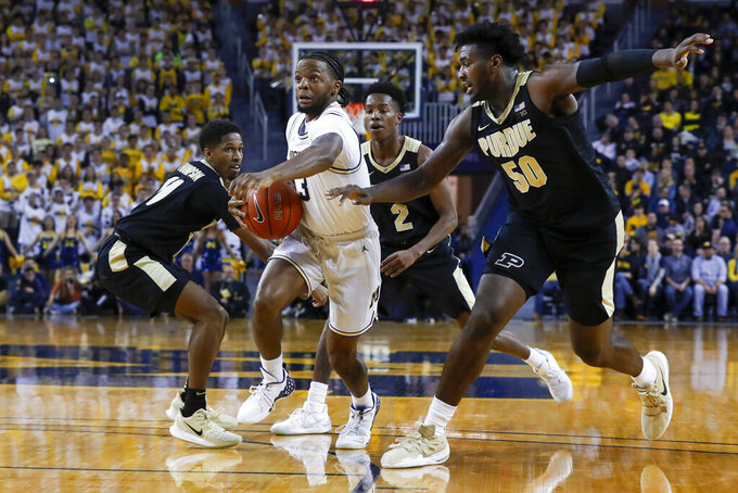 Michigan guard Zavier Simpson (3) drives next to Purdue forward Trevion Williams (50) during the second half of an NCAA college basketball game in Ann Arbor, Mich., Thursday, Jan. 9, 2020. (AP Photo/Paul Sancya)