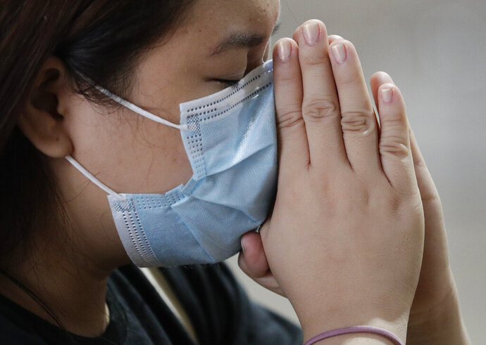 In this Feb. 10, 2020, photo, a Catholic woman wearing a face mask prays during a mass at the Minor Basilica of San Lorenzo Ruiz in Manila's Chinatown, Philippines. In a popular Catholic church in Manila, nearly half of the pews were empty for Sunday Mass. The few hundred worshippers who showed up, some in protective masks, have been asked to refrain from shaking or holding hands in prayers. (AP Photo/Aaron Favila)