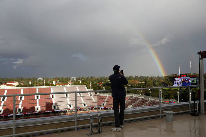 FILE - In this Nov. 26, 2016, file photo, a man photographs a rainbow over Stanford Stadium before an NCAA college football game between Stanford and Rice in Stanford, Calif. The return of football isn't likely to make much of a dent in the losses athletic departments across the Pac-12 will ultimately incur because of the coronavirus pandemic. Faced with dramatic budget shortfalls, most schools in the league have already resorted to layoffs, furloughs, and cutting some sports entirely. The most dramatic action was taken by Stanford, which is discontinuing 11 varsity sports programs at the end of 2020-21. (AP Photo/Marcio Jose Sanchez, File)