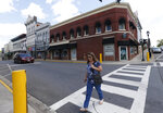 In this May 6, 2019, photo, a pedestrian crosses the street in front of the old Green's drugstore that is the site a tribute center for the Bedford Boys in Bedford, Va. The 75th anniversary of the D-Day invasion of Normandy has a solemn significance for Bedford, who lost 20 local men. (AP Photo/Steve Helber)