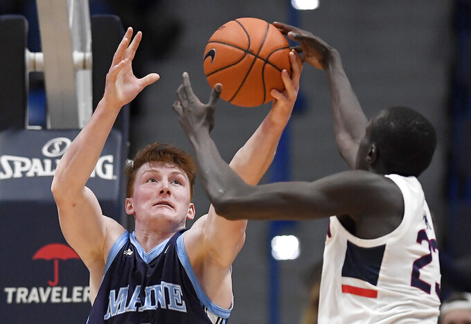 Maine's Andrew Fleming grabs a rebound against Connecticut's Akok Akok, right, during the second half of an NCAA college basketball game Sunday, Dec. 1, 2019, in Hartford, Conn. (AP Photo/Jessica Hill)