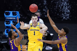 Michigan center Hunter Dickinson (1) passes over LSU guard Javonte Smart, left, during the first half of a second-round game in the NCAA men's college basketball tournament at Lucas Oil Stadium Monday, March 22, 2021, in Indianapolis. (AP Photo/AJ Mast)