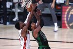 Miami Heat forward Bam Adebayo, left, contest a shot by Boston Celtics guard Marcus Smart, right, during the second half of an NBA conference final playoff basketball game, Thursday, Sept. 17, 2020, in Lake Buena Vista, Fla. (AP Photo/Mark J. Terrill)