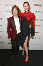 FILE - Mick Jagger and girlfriend designer L'Wren Scott attend Harper's Bazaar Women of the Year Awards 2013 on Nov. 5, 2013, in London. The dress worn by Scott is among 55 L'Wren Scott creations going on sale this week at Christie's in London. (Photo by Jon Furniss/Invision for Harper's Bazaar/AP)