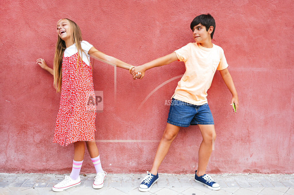 Cheerful friends holding hands while standing on footpath