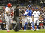 Milwaukee Brewers catcher Manny Pina has work with Cincinnati Reds' Derek Dietrich as he is walked to first after being hit by a pitch during the seventh inning of a baseball game Friday, June 21, 2019, in Milwaukee. (AP Photo/Morry Gash)