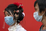 Residents wearing masks to help curb the spread the coronavirus walk along a retail street in Wuhan in central China's Hubei province, Thursday, April 9, 2020. Released from their apartments after a 2 1/2-month quarantine, residents of the city where the coronavirus pandemic began are cautiously returning to shopping and strolling in the street but say they still go out little and keep children home while they wait for schools to reopen. (AP Photo/Ng Han Guan)