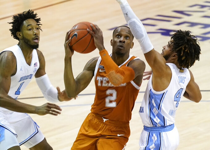 Texas guard Matt Coleman III (2) takes aim at the basket between North Carolina guard Leaky Black (1) and guard R.J. Davis (4) in the first half of an NCAA college basketball game for the championship of the Maui Invitational, Wednesday, Dec. 2, 2020, in Asheville, N.C. Texas won 69-67. Coleman was the MVP with the winning basket and high score of 22 points. (AP Photo/Kathy Kmonicek)