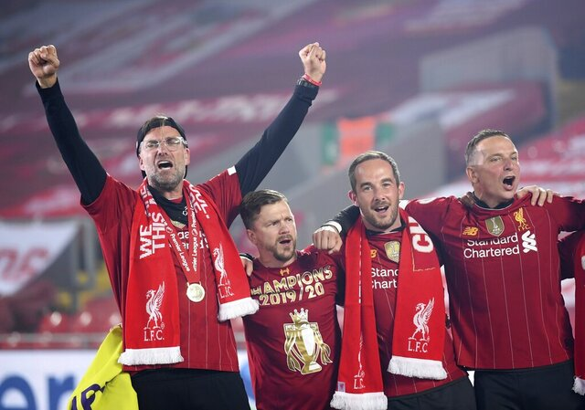 Liverpool's manager Jurgen Klopp, left, celebrates following the English Premier League soccer match between Liverpool and Chelsea at Anfield Stadium in Liverpool, England, Wednesday, July 22, 2020. Liverpool are champions of the EPL for the season 2019-2020. The trophy is presented at the teams last home game of the season. Liverpool won the match against Chelsea 5-3. (Laurence Griffiths, Pool via AP)