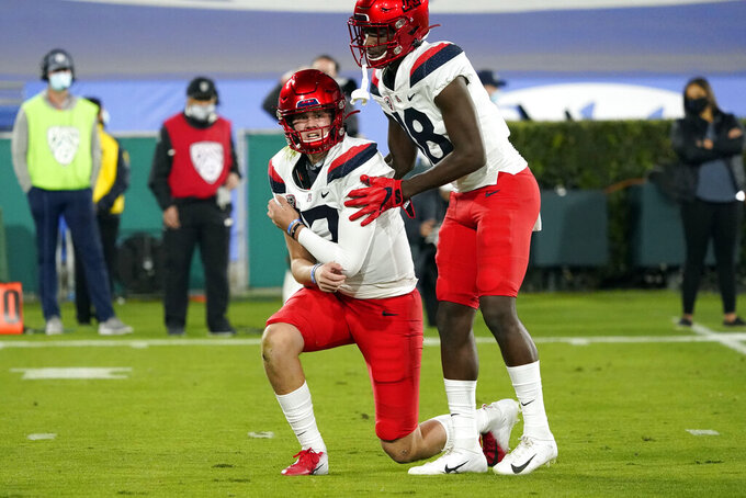 Arizona quarterback Grant Gunnell, left, holds his shoulder next to wide receiver Ma'jon Wright after being shoved to the ground on the first play from scrimmage during the first half of an NCAA college football game against UCLA, Saturday, Nov. 28, 2020, in Pasadena, Calif. (AP Photo/Marcio Jose Sanchez)