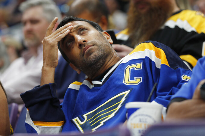 A St. Louis Blues fan looks at the scoreboard during the first period of Game 3 of the NHL hockey Stanley Cup Final between the Blues and the Boston Bruins Saturday, June 1, 2019, in St. Louis. (AP Photo/Jeff Roberson)