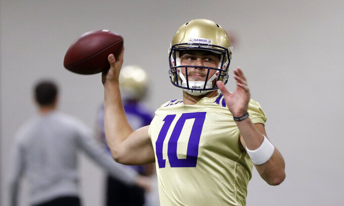 FILE - In this Aug. 5, 2019, file photo, Washington quarterback Jacob Eason readies a throw during an NCAA football practice in Seattle. In his tenure at Washington, Chris Petersen has faced situations where the Huskies lose a significant chunk of talent to the next level, only to replenish and continue what's been an upward trend during his first five seasons in charge.  This season will test whether the Huskies can simply continue to reloadThey could have Georgia transfer Jacob Eason _ once the top recruit in the country coming out of high school _ under center at quarterback. (AP Photo/Elaine Thompson, File)