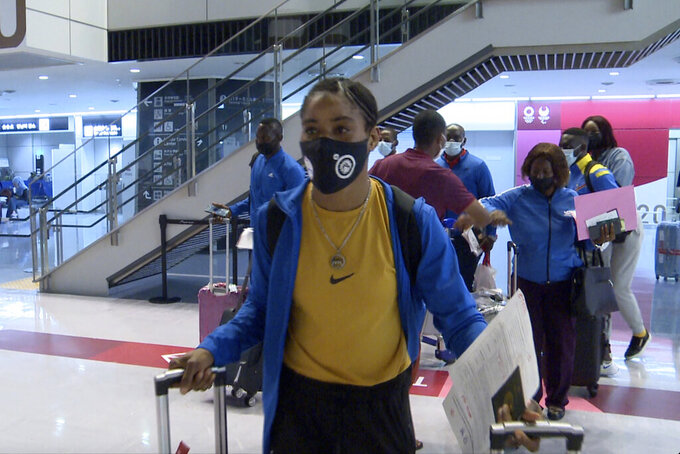 In this image made from a video, Guinean freestyle wrestler Fatoumata Yarie Camara, foreground, arrives with a delegation of athletes, at Narita International Airport in Narita, east of Tokyo, Sunday, July 25, 2021. A West African wrestler's dream of competing in the Olympics has come down to a plane ticket. Fatoumata Yarie Camara is the only Guinean athlete to qualify for these Games. She was ready for Tokyo, but confusion over travel reigned for weeks. The 25-year-old and her family can't afford it. Guinean officials promised a ticket, but at the last minute announced a withdrawal from the Olympics over COVID-19 concerns. Under international pressure, Guinea reversed its decision.  (AP Photo/Alessandro Libri)