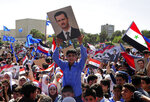 In this photo released by the Syrian official news agency SANA, protesters wave flags and portraits of President Bashar Assad, as they march during a demonstration to show solidarity with the Syrian armed forces, at Omayyad Square, in Damascus, Syria, Monday, April 16, 2018. Hundreds of Syrians have gathered in support of their armed forces, which they say succeeded in confronting the unprecedented joint airstrikes by the West over the weekend. (SANA via AP)
