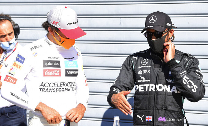 Mercedes driver Lewis Hamilton, right, of Britain, talks with third placed Mclaren driver Carlos Sainz, of Spain, after clocking the fastest time during the qualifying session for Sunday's Italian Formula One Grand Prix, at the Monza racetrack in Monza, Italy, Saturday, Sept. 5, 2020. (Jennifer Lorenzini/Pool via AP)
