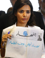 Nayla Tueni, the editor-in-chief of An-Nahar daily newspaper, holds a copy of a blank published newspaper in a strong protest against the paralysis in the country and politicians' inability to form a government, at the paper's headquarters, in downtown Beirut, Lebanon, Thursday, Oct. 11, 2018. Tueini said the decision to run an empty paper was An-Nahar's way of expressing its exasperation with Lebanon's status quo. The Arabic blue words reads: