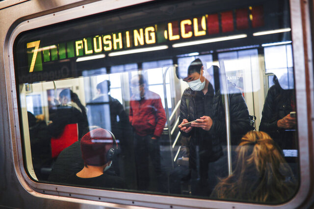 FILE - In this April 7, 2020, file photo, some people wear masks while using the New York City subway system during the coronavirus pandemic in New York. New York's mass transit agency wants Apple to come up with a better way for iPhone users to unlock their phones without taking off their masks, as it seeks to guard against the spread of COVID-19 in buses and subways. (AP Photo/John Minchillo, File)