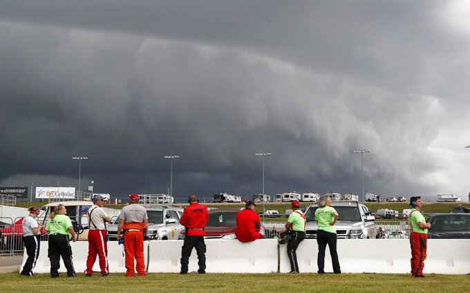 Track workers watch storms clouds move in over the track before a NASCAR Truck Series auto race, Saturday, June 15, 2019, at Iowa Speedway in Newton, Iowa. (AP Photo/Charlie Neibergall)