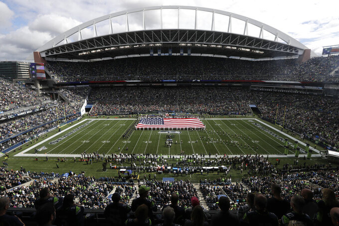 A United States flag is displayed at CenturyLink Field during the singing of the national anthem before an NFL football game between the Seattle Seahawks and the Cincinnati Bengals, Sunday, Sept. 8, 2019, in Seattle. (AP Photo/Stephen Brashear)