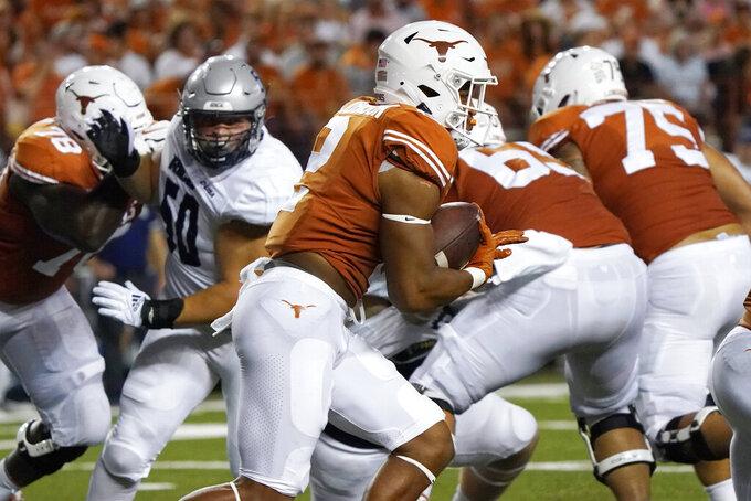 Texas running back Roschon Johnson (2) breaks through the line as he runs for a touchdown against Rice during the first half of an NCAA college football game Saturday, Sept. 18, 2021, in Austin, Texas. (AP Photo/Chuck Burton)