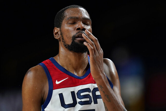 United States's Kevin Durant reacts after he collided with another player and hit his face during a men's basketball preliminary round game against the Czech Republic at the 2020 Summer Olympics, Saturday, July 31, 2021, in Saitama, Japan. (AP Photo/Eric Gay)