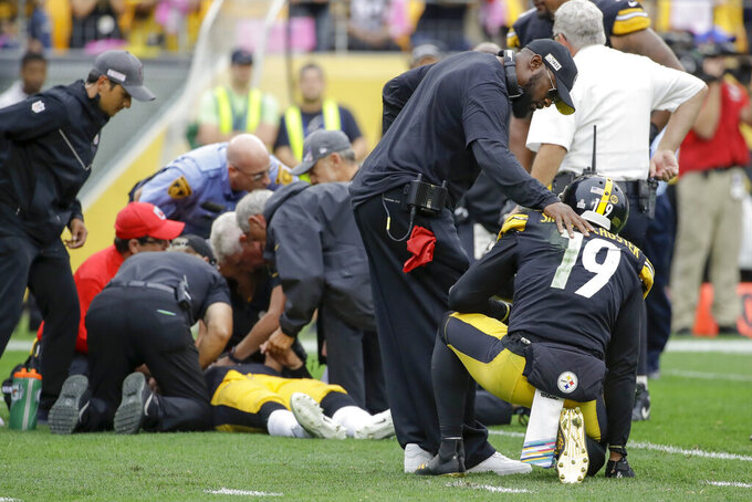 Pittsburgh Steelers head coach Mike Tomlin, front left, consoles wide receiver JuJu Smith-Schuster (19) after quarterback Mason Rudolph, back left, is tended to after getting injured in the second half of an NFL football game against the Baltimore Ravens, Sunday, Oct. 6, 2019, in Pittsburgh. (AP Photo/Don Wright)