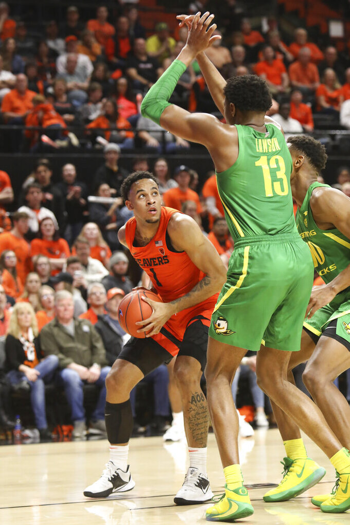 Oregon State's Sean Miller-Moore (1) looks for a path around Oregon's Chandler Lawson (13) and Shakur Juiston (10) during the first half of an NCAA college basketball game in Corvallis, Ore., Saturday, Feb. 8, 2020. (AP Photo/Amanda Loman)