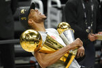 Milwaukee Bucks forward Giannis Antetokounmpo reacts while holding the NBA Championship trophy, left, and Most Valuable Player trophy after defeating the Phoenix Suns in Game 6 of basketball's NBA Finals in Milwaukee, Tuesday, July 20, 2021. The Bucks won 105-98. (AP Photo/Paul Sancya)