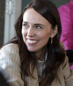 New Zealand Prime Minister Jacinda Ardern reacts as she talks with colleagues at a cafe in Auckland, New Zealand, Sunday, Oct. 18, 2020. Ardern has won a second term in office in an election landslide of historic proportions. (AP Photo/Mark Baker)
