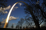 In this Tuesday, April 7, 2020 photo, the setting sun reflects off the north leg of the Gateway Arch in St. Louis. Stay-at-home orders and social distancing have reduced tourism at places like the Arch which was seeing surges in visitors thanks to its newly-renovated grounds and expanded museum. The park grounds are still open but the museum and tram to the top of the monument are closed until further notice due to the coronavirus outbreak. (AP Photo/Jeff Roberson)