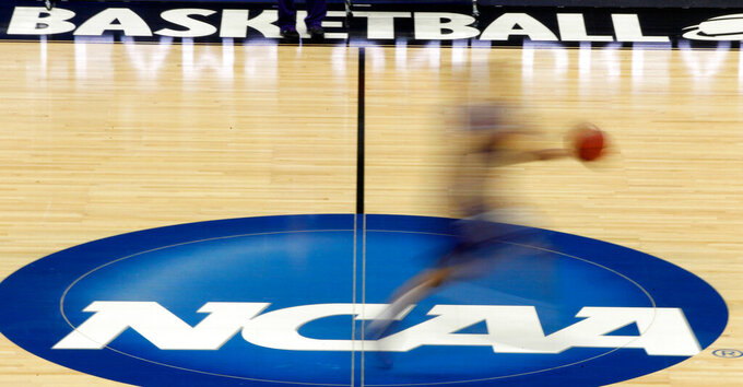 FILE - In this March 14, 2012, file photo, a player runs across the NCAA logo during practice in Pittsburgh before an NCAA tournament college basketball game. The Associated Press has learned that the NCAA has not tested players for performance-enhancing drugs while they've been at March Madness and other recent college championships. Three people familiar with testing protocols tell AP full-scale testing has not resumed since the coronavirus pandemic shut down college sports a year ago.  (AP Photo/Keith Srakocic, File)
